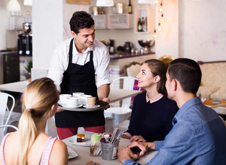 Polite smiling waiter bringing ordered dishes to friends in tearoom