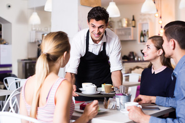 Polite happy waiter bringing ordered dishes to friends in tearoom