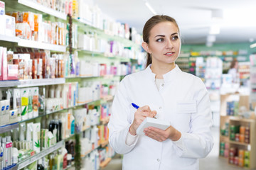 Young woman is attentively checking medicine with notebook