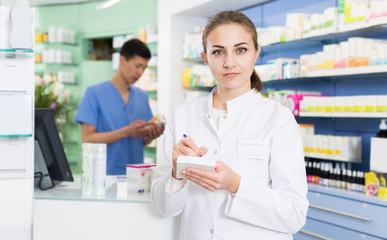 Young female pharmacist is attentively checking medicine to notebook