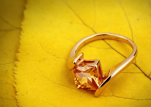 Jewelry ring with gemstone on yellow leaves background, copy space