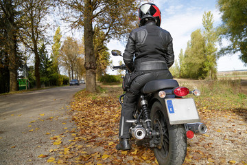 Rear view of a biker girl parked on the side of the road