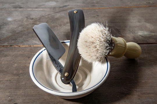 straight razor with shaving brush in bowl on rustic wood