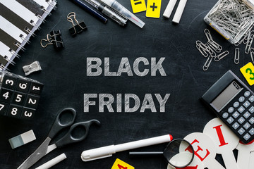 Black Friday banner with white chalk text on blackboard with  stationery and office accessories.  Black friday sale