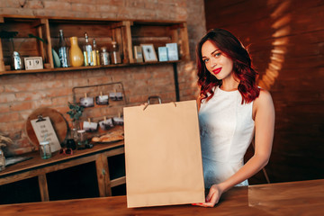 Housewife female chef cook baker in striped apron t-shirt toque chefs hat isolated on red wall background.Woman hold in hand brown clear blank craft paper bag takeaway Mock up copy space concept