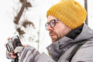 Bearded male photographer in warm clothes takes pictures of the winter landscape, on a blurred background a rock covered with snow in a cloudy winter day. Close-up.