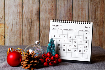 December 2019 calendar and Christmas decoration - baubles, cone and rowanberry on the soft table and wooden wall in the background