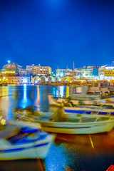 Panorama of Old Venetian Harbour with Lines of Ships and Boats At Blue Hour in Heraklion City in Greece. Blurred Motion of The Boats Due to Wind and Sea Waves On Foreground.