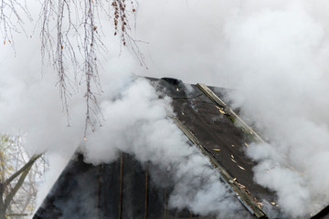 White smoke comes from the burning roof of the house