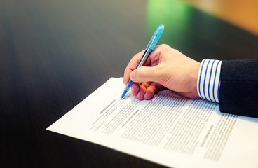 Cropped closeup of a man hand filling in Non Disclosure Agreement (NDA). Reading and signing business concept