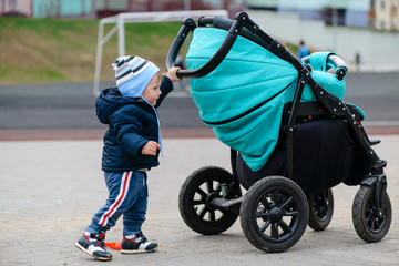 baby boy pushing his stroller on the street