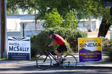 A man rides a bicycle past campaign signs for Arizona U.S. senatorial candidates Krysten Sinema and Martha McSally following the U.S. Midterm elections in Scottsdale, Arizona