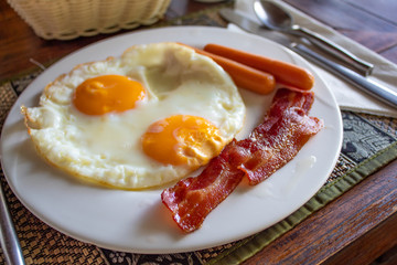 Delicious English Breakfast with fried eggs, sausages, bacon, jam and more