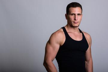 Studio shot of young muscular Persian man wearing sleeveless aga