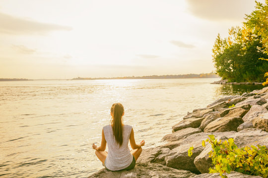 Yoga class outside in nature park by lake river shore. Woman sitting in lotus pose meditating by the water in morning sun flare sunrise. Meditation wellness.
