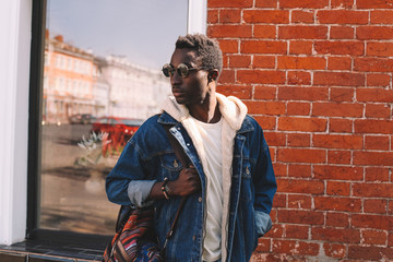 Wall Mural - Fashion african man in jeans jacket, with backpack walking on city street, brick wall background