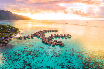 Poster Oceania Luxury travel vacation aerial of overwater bungalows resort in coral reef lagoon ocean by beach. View from above at sunset of paradise getaway Moorea, French Polynesia, Tahiti, South Pacific Ocean.