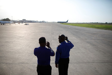 Two security officers take pictures of a Chilean Air Force plane transporting 176 Haitians returning from Chile at their arrival to the International Airport of Port-au-Prince