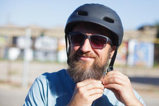 man fastening bicycle helmet