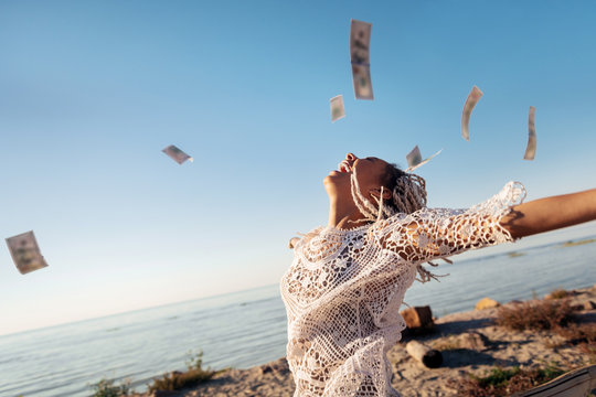 Money in air. Successful prosperous freelancer with white dreadlocks throwing her money in the air