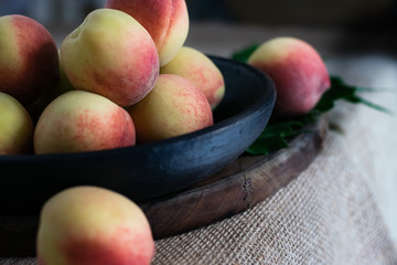 Fresh peaches fruits with in black plate on dark wooden rustic background, angle view