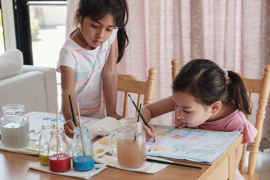 Young multiethnic  girls painting watercolor, montessori homeschool education