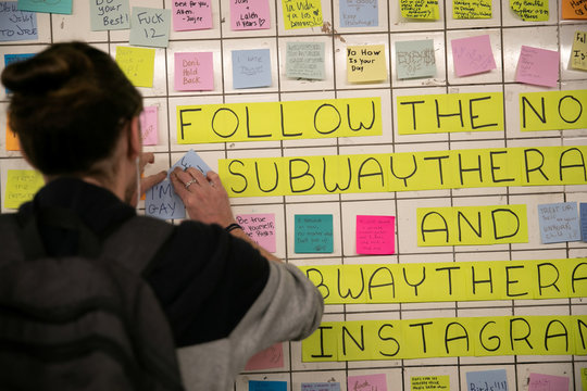 A commuter pastes a message written on a Post-it note in the Union Sq subway station in New York City,