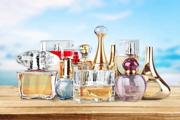 Aromatic Perfume bottles on wooden table on blurred background