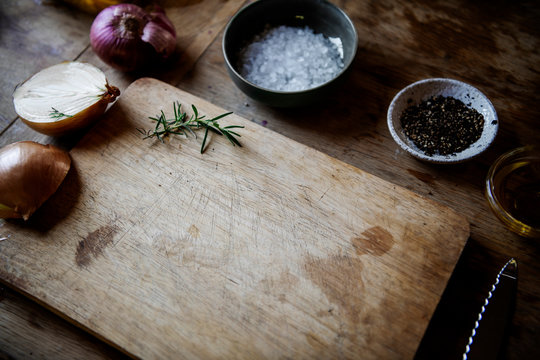 Empty wooden chopping board with spices and herbs