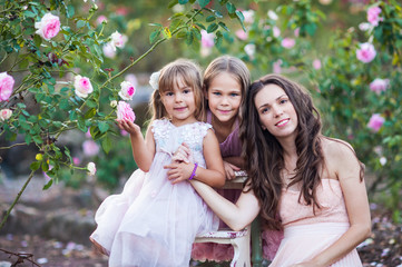 Lovely family mum and daughters in a blooming flower garden