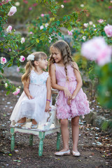 Beautiful children on a girls party in a blooming rose garden