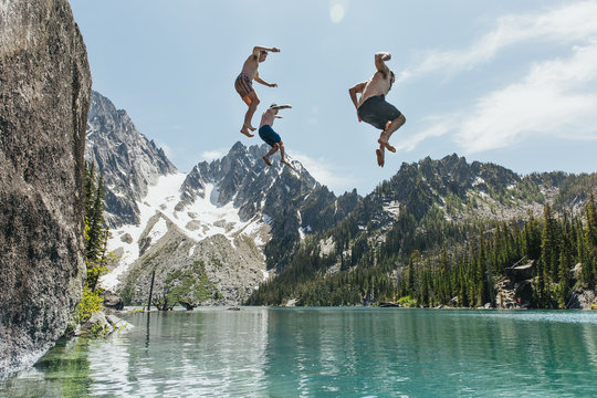 Young men jumping from cliff into lake