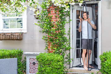 Young man, house, entering exiting outdoor spring garden with plant flowers covering brick wall in backyard porch of home by door, insect mosquito pest net