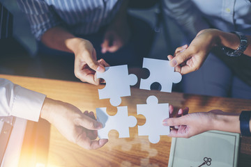 Business people putting connect jigsaw puzzle. Team work and strategic solution concept. top view.
