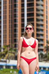Young woman on beach during sunny day with red sunglasses bikini in Miami, Florida with skyscrapers hotels apartments urban background, happy smiling, tanning skin
