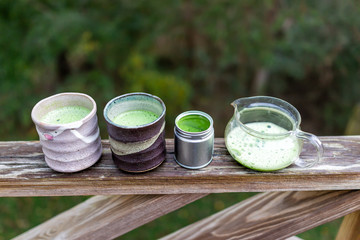 Glass teapot on wooden railing outside on backyard deck garden, two cups filled with Japanese vibrant green tea color matcha, foam in morning