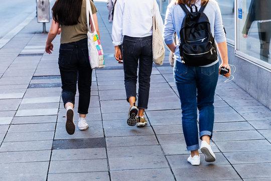 legs of young women walking on the sidewalk