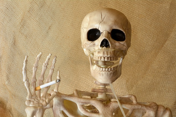 Skeleton holding lit cigarette with hand and canula for oxygen attached to nasal cavity