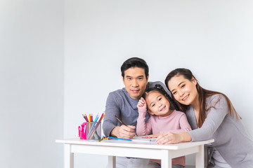 Asian family girl kid, mother and father doing drawing with many colour pencils on white paper over white background