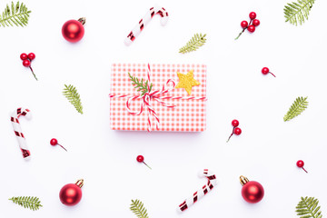 Christmas background concept. Top view of Christmas gift box red sock with spruce branches, pine cones, red berries and bell on white background.