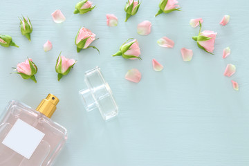 Top view image of perfume bottle with rose petals flowers over pastel blue background. Floral scent concept.