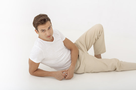 Young casual man looking pensive while lying down on white background. Guy looking at camera in studio