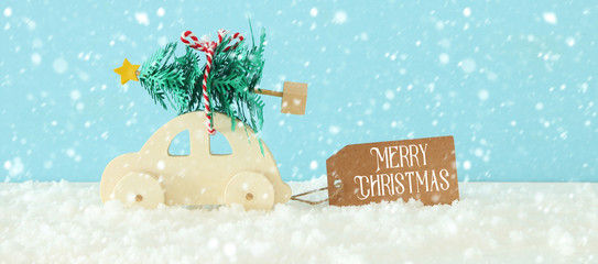 Wooden car carrying a christmas tree in front of blue background.