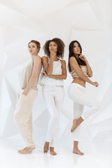 Group of friends of different race. Diverse women standing together against white polygon background indoors. Multi ethnic females in full lenght looking at camera in studio.
