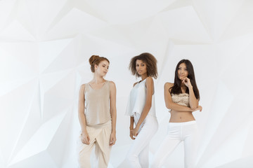 Group of friends of different race. Diverse women standing together against white polygon background indoors. Multi ethnic females looking at camera in studio.