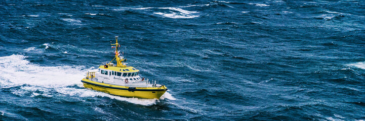 Coast guard boat patrol riding on rough sea waves in Alaska. Panoramic banner background.