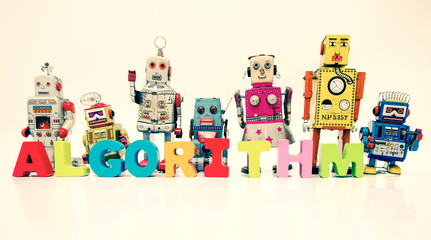 The word ALGORITHM  with wooden letters and retro robot toys