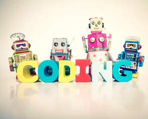 a team of toy robots with the word coding isolated