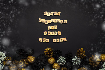 Pine cones and nuts painted in golden, black, white colors on a black background. Added text Happy New Year and Merry Christmas. Flat lay, top view