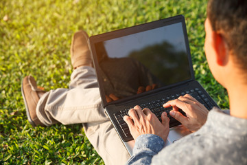 Businessman sitting on grass is working on laptop in the park. Wall mural